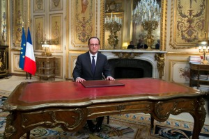 French President Francois Hollande delivers his New Year's wishes during a pre-recorded address to the nation at the Elysee Palace in Paris on December 31, 2014.  AFP PHOTO / POOL / IAN LANGSDON